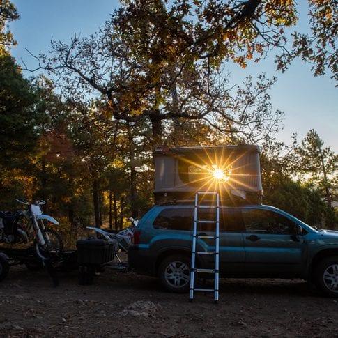 camping car towing motorcycles at sunset