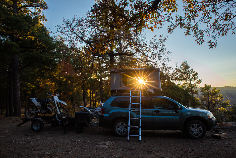 camping car towing motorcycles at sunset