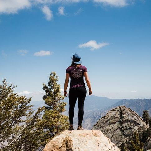woman standing on mountain ledge