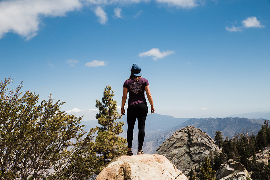 woman standing on mountain ledge
