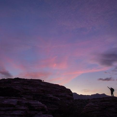 man pointing during sunset at red rocks