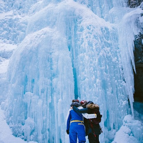 two girls hugging in front of frozen waterfall