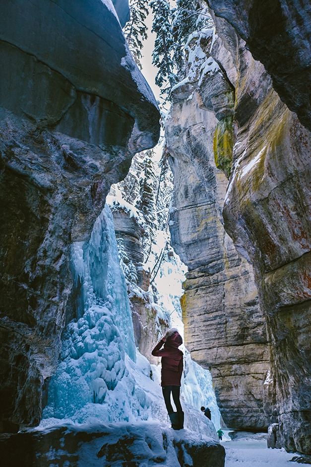 girl standing in canyon with frozen waterfalls